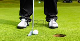 20053389-golf-player-putting-ball-into-hole-only-feet-and-iron-to-be-seen